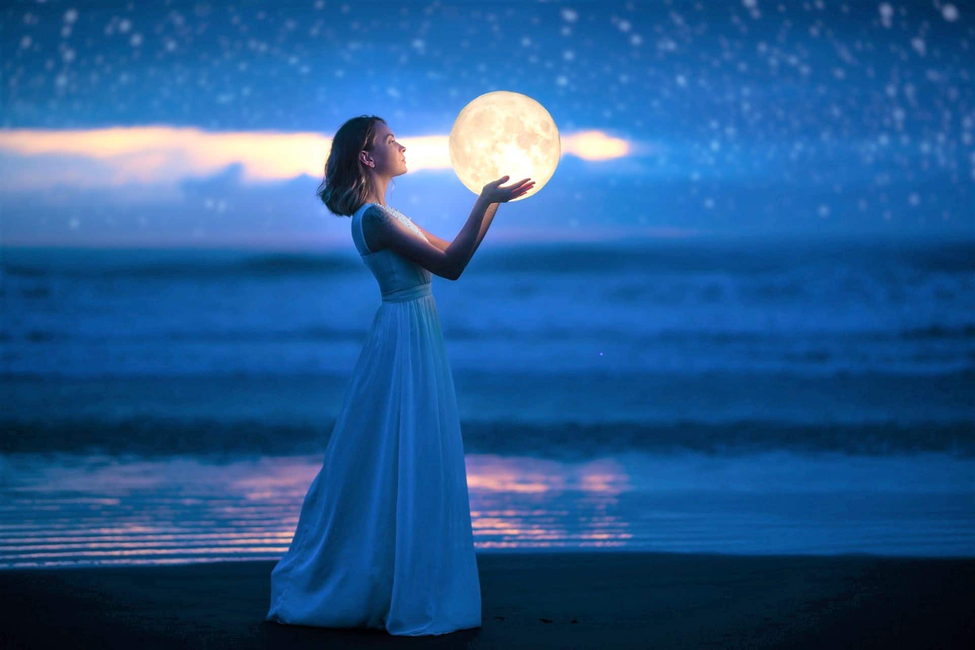 A young girl on a night beach holds the moon, with a starry sky