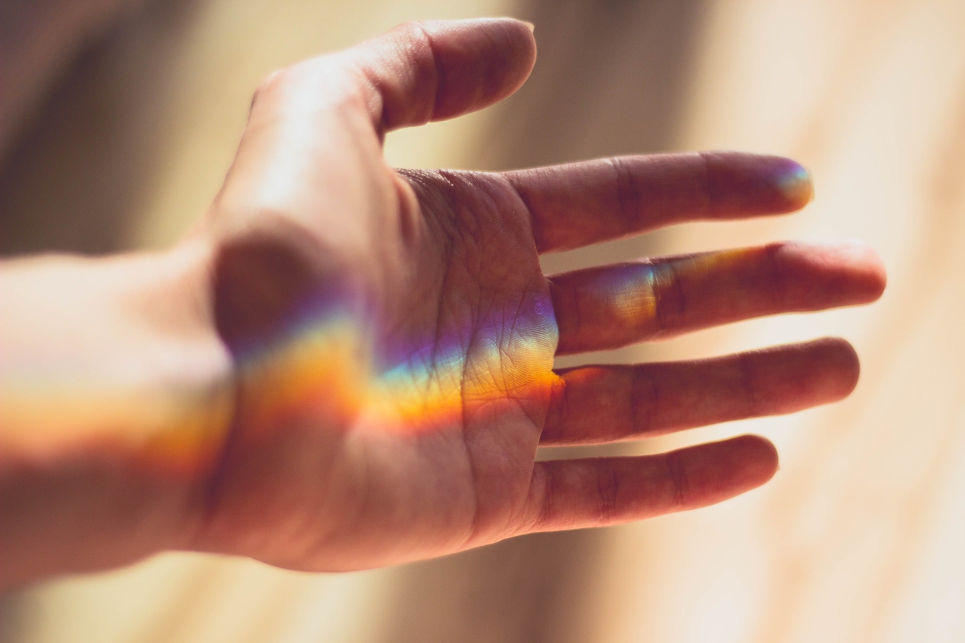 light of rainbow reflecting on a hand