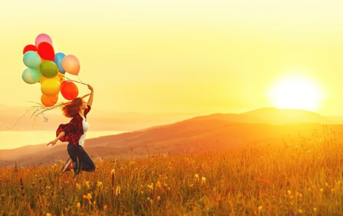 Happy cheerful girl with balloons running across meadow at sunset