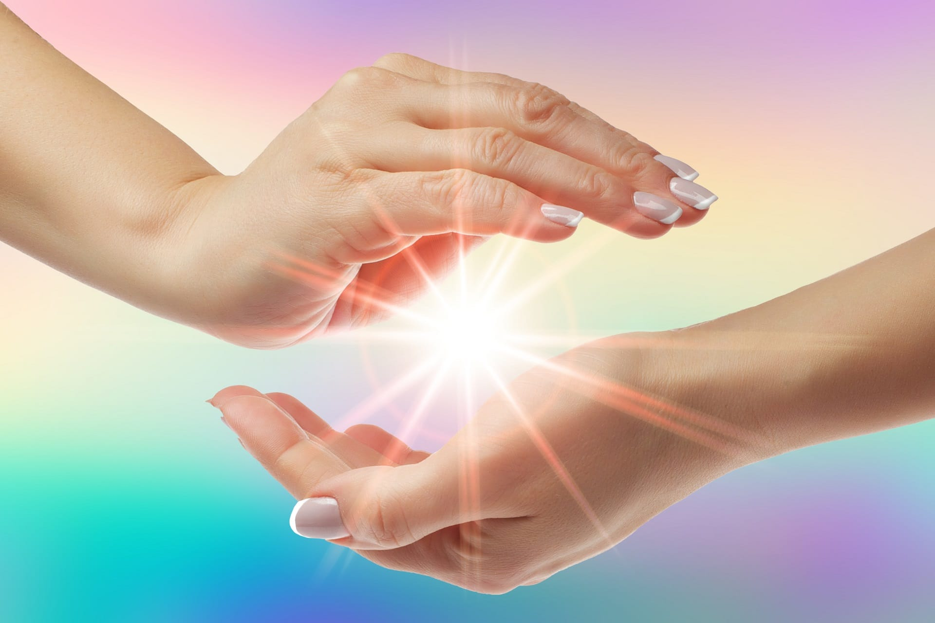 Women healing hands with bright sunburst on rainbow background