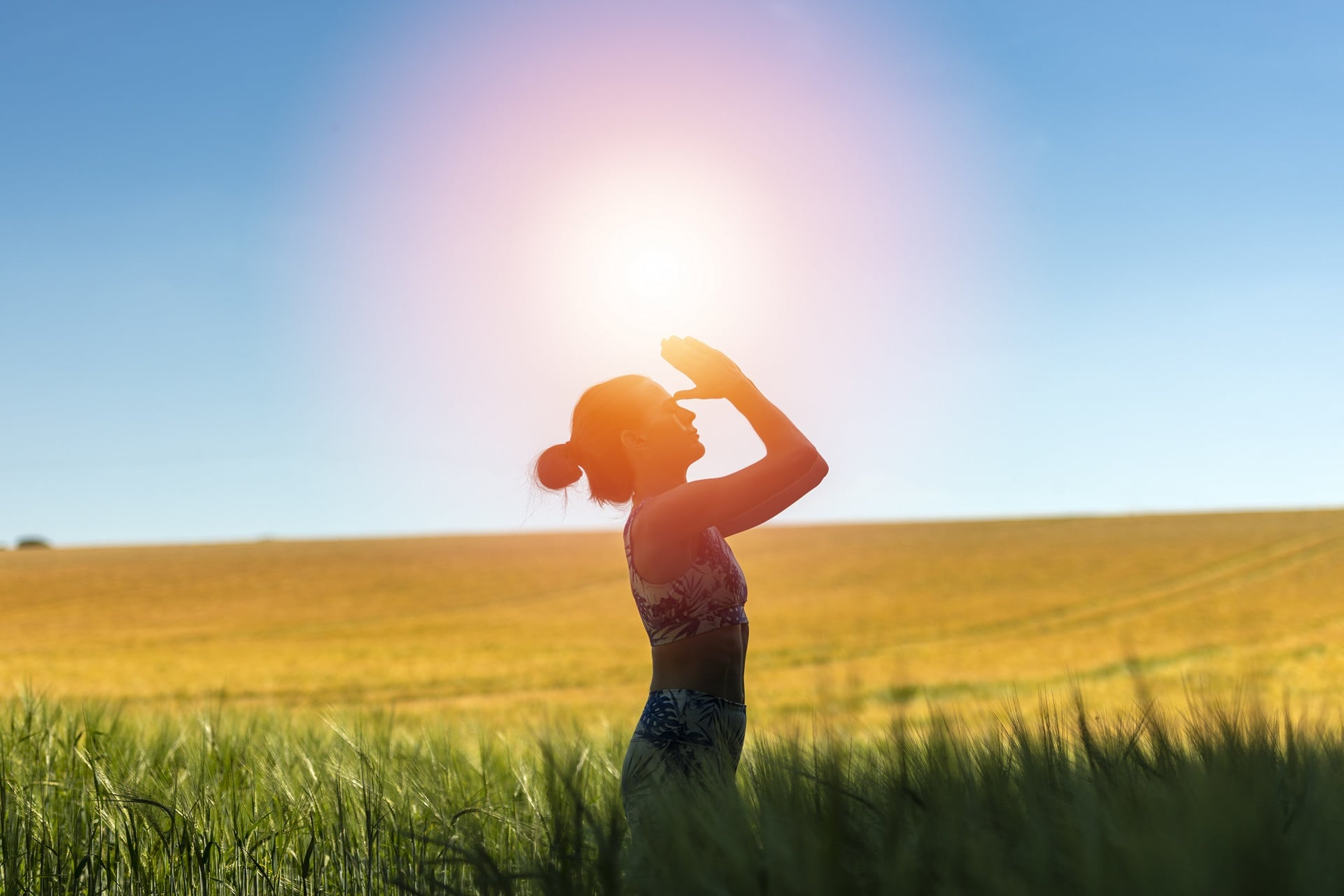 woman standing in a field meditating, yoga pose.