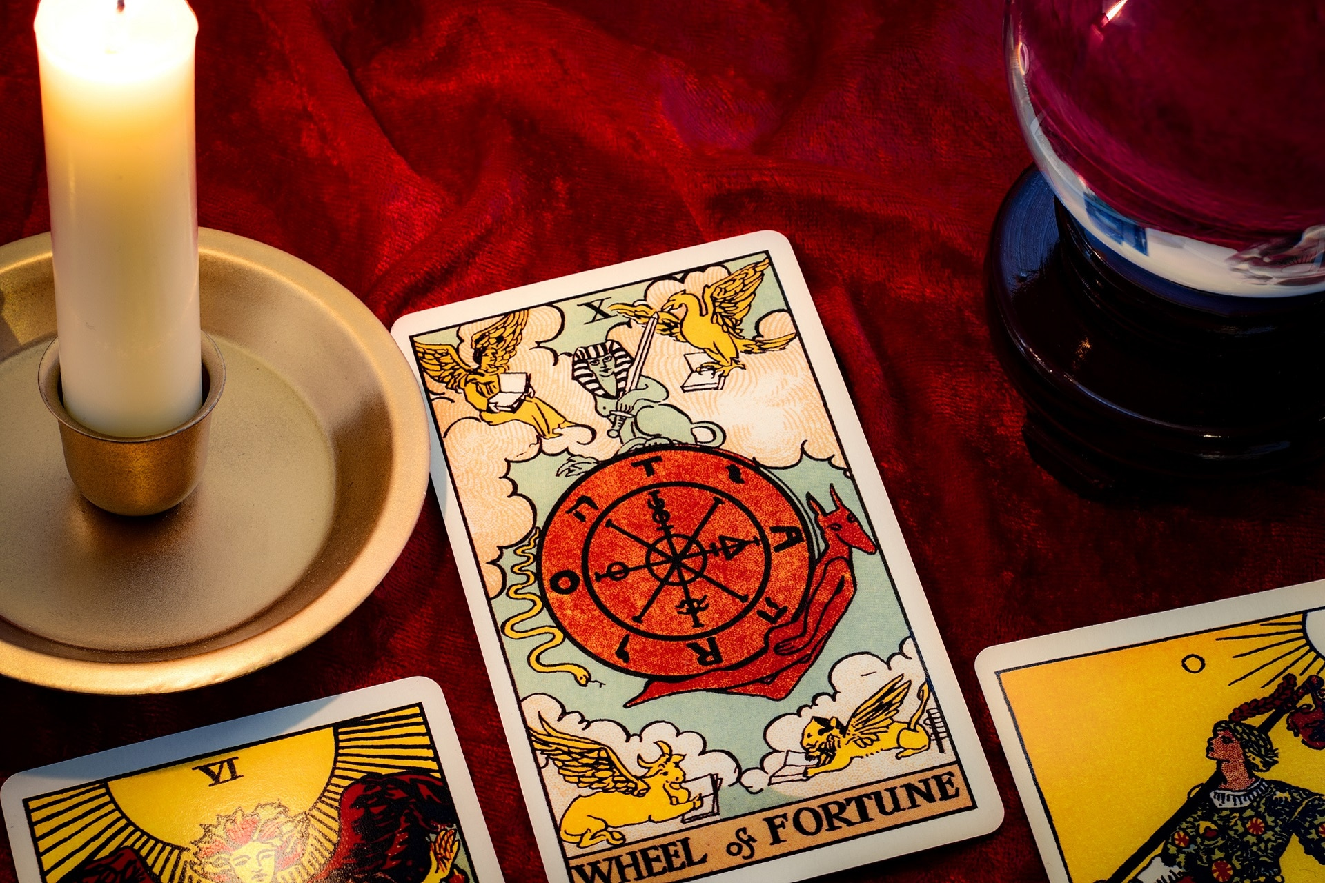 Wheel of fortune card and crystal ball under candle light. Cartomancy is fortune telling using cards, while scrying and clairvoyance is future reading using orbs, both are branches of astrology