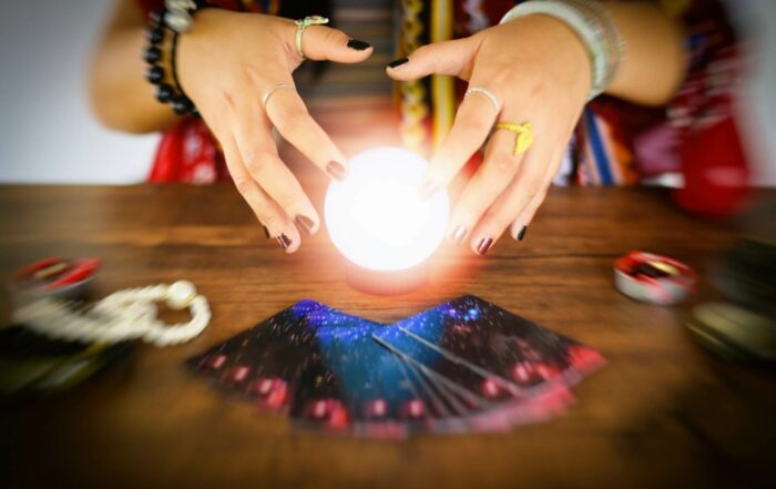 Psychic readings and clairvoyance concept - Crystal ball fortune teller hands and Tarot cards reading