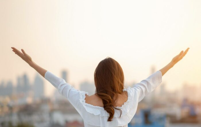 woman raised hands up in the air over city background while standing at outdoor.