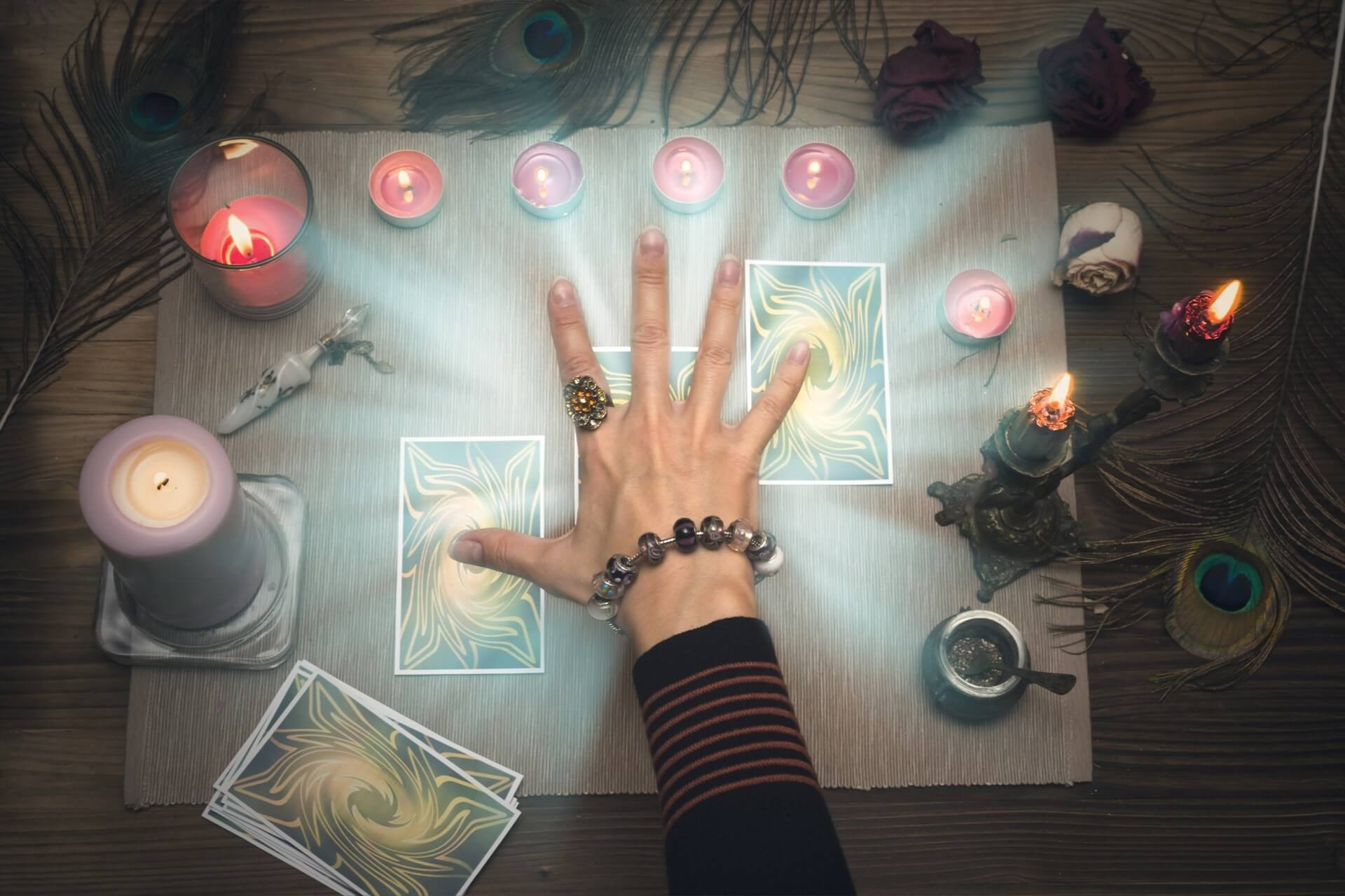 A psychic reader surrounded by tarot cards and candles