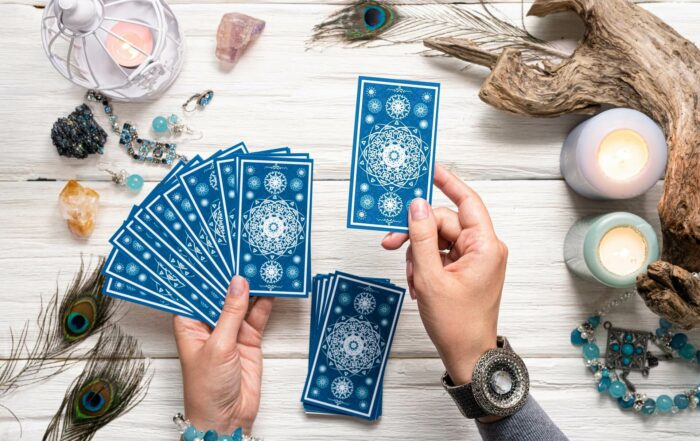 a Tarot reader picking up tarot cards against a white background